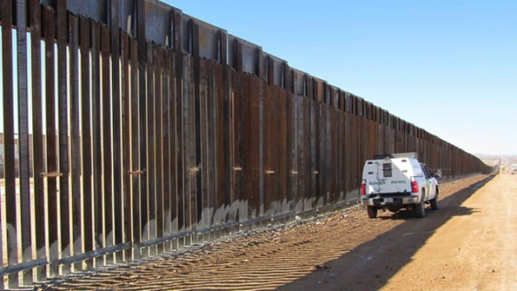A border patrol vehicle observes six miles of border fencing in Douglas, Arizona