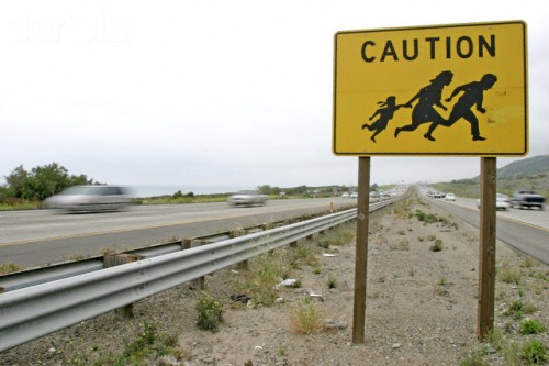Sign Warning of Illegal Immigrants Crossing Road